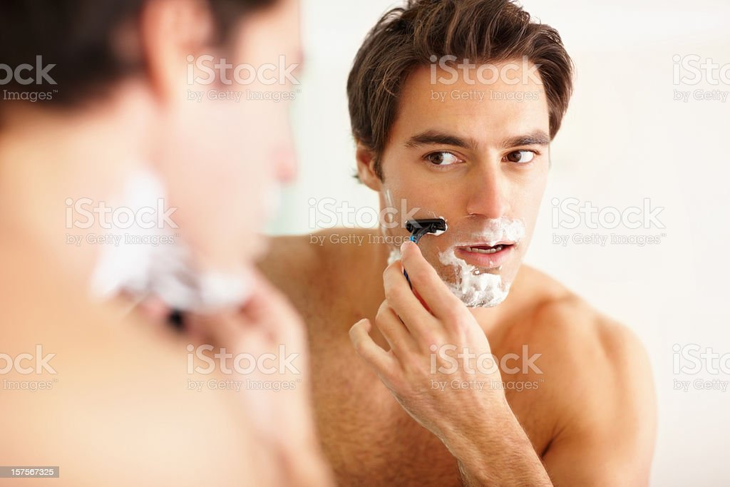 Young guy shaving in the bathroom with a razor royalty-free stock photo
