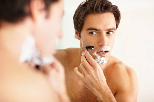 Young guy shaving in the bathroom with a razor stock photo