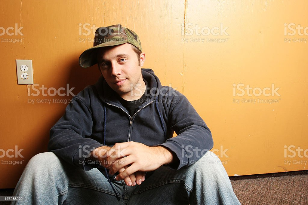 Young Guy Sitting Against an Orange Wall royalty-free stock photo
