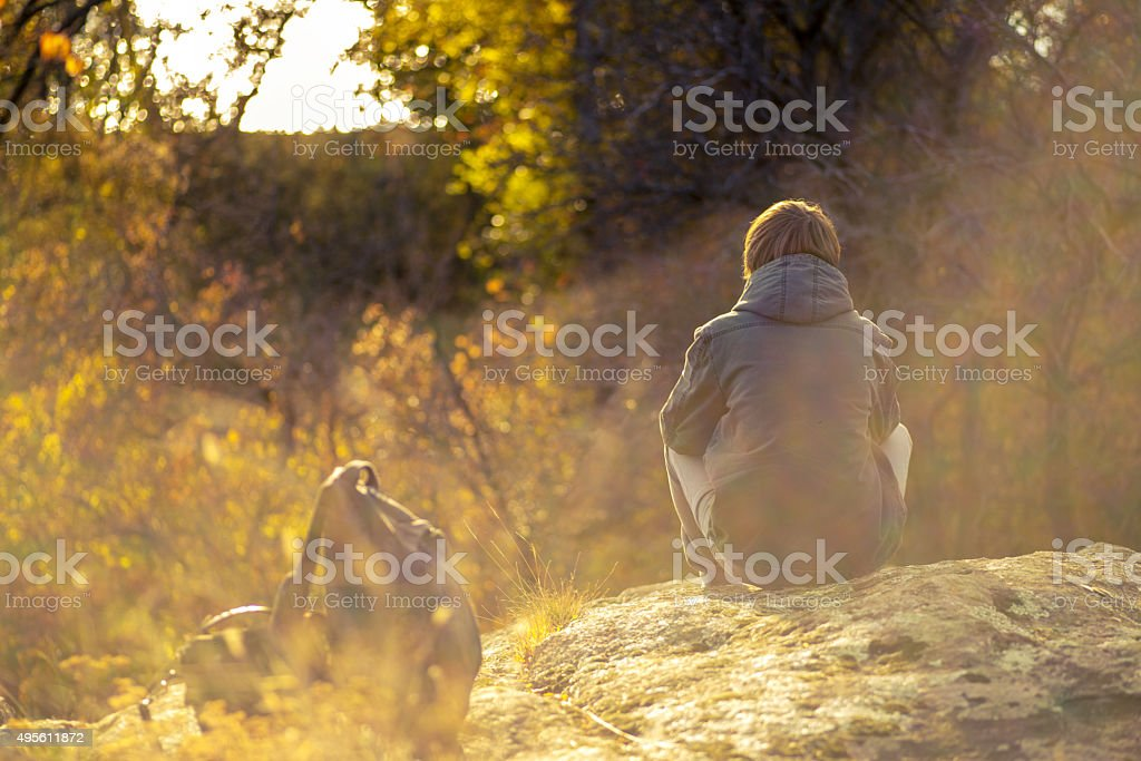 young guy sitting on a rock stock photo