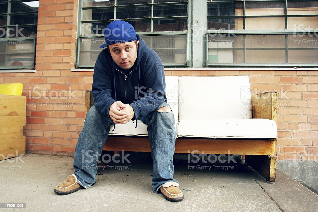 Young Guy Sitting on an Old Couch Outside royalty-free stock photo