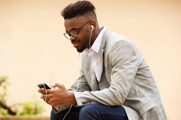 jeune homme assis à l'extérieur d'écouter de la musique avec téléphone portable - écouteurs intra auriculaires photos et images de collection