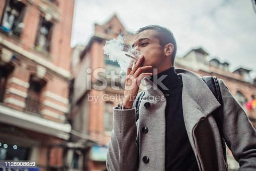 Fashionable handsome man wearing gray coat and black backpack, smoking cigarette.