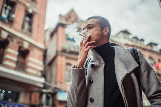 Young guy smoking on the street stock photo