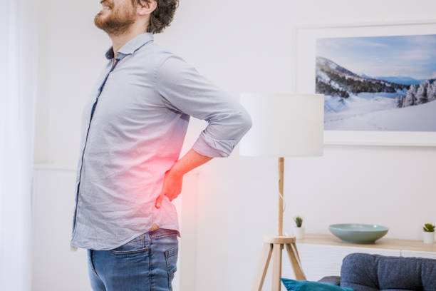 Young guy suffering from backache at home stock photo