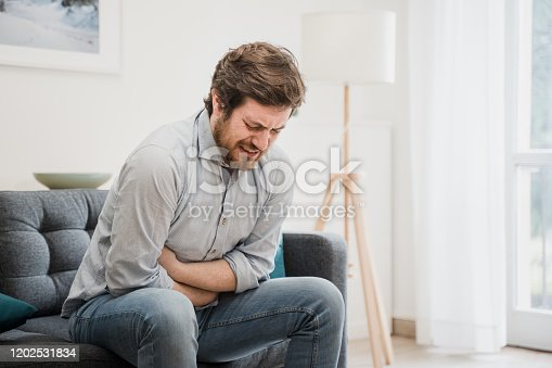 istock Young guy suffering from stomachache at home 1202531834