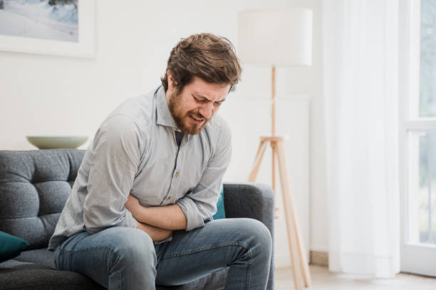 Young guy suffering from stomachache at home stock photo