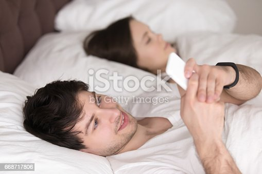 660634310 istock photo Young guy using mobile phone while girlfriend sleeping in bed 668717806