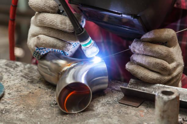 穿著方格紅襯衫的年輕焊工用農藝焊接焊接不銹鋼管,用鐵車間的面罩保護他的眼睛。現代焊接方法。圖像檔