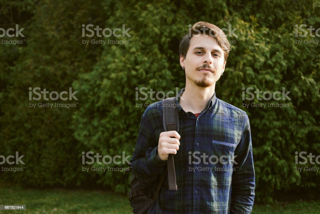 Young guy with a backpack in the park, green background stock photo