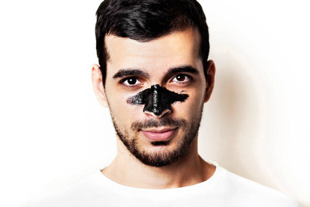 Young guy with a black charcoal mask on his face on white background, Young and beautiful man with black peel-off mask on her face, stock photo