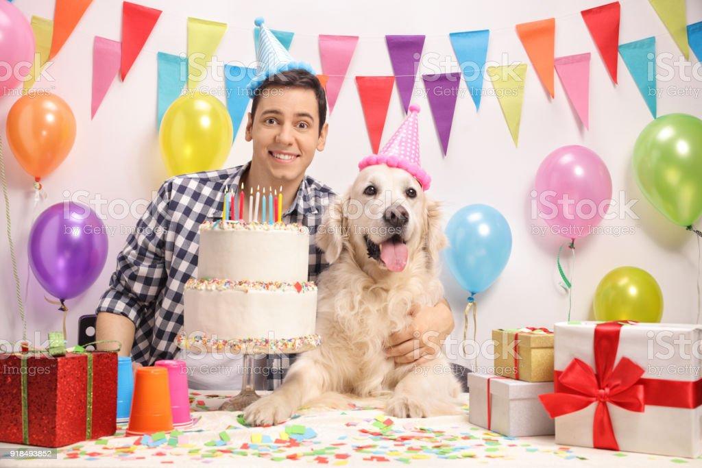 Young guy with a labrador retriever dog celebrating a birthday