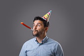 istock Young guy with party hat 947340426