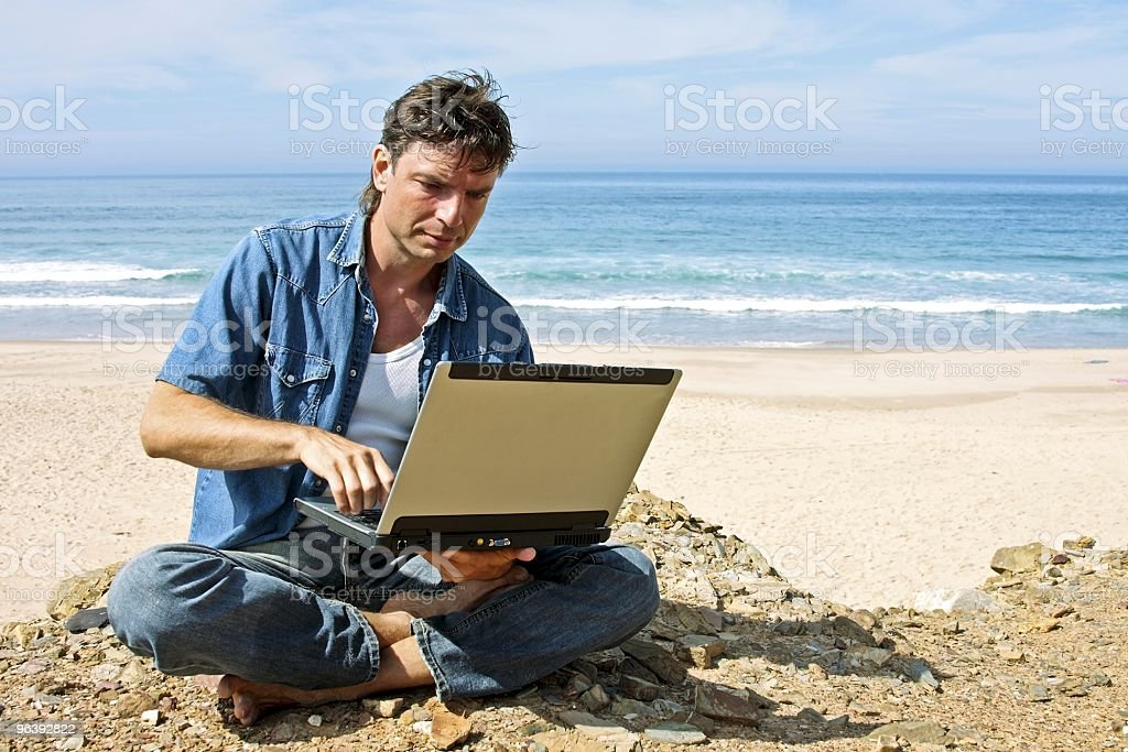 Young guy working on his laptop at the atlantic ocean royalty-free stock photo