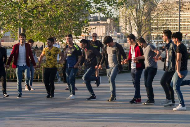 junge kerle tanzen zu musik auf dem bosporus-ufer im stadtteil üsküdar - kurdische sprache stock-fotos und bilder