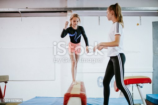 Young gymnast balancing on a balance beam