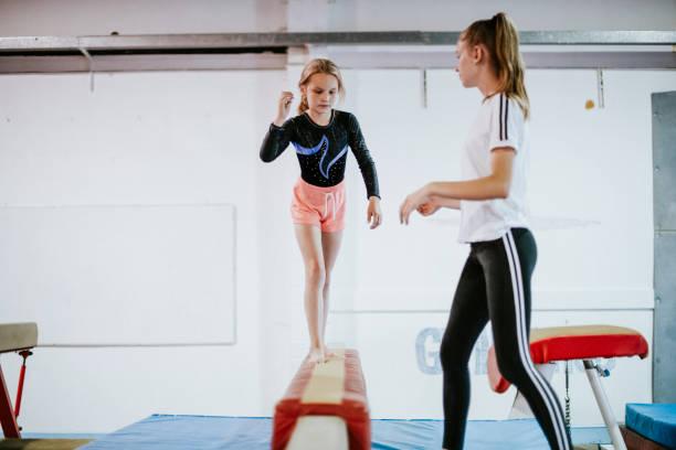 joven gimnasta equilibrio sobre una viga de equilibrio - gimnasia fotografías e imágenes de stock