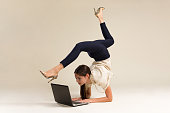 istock Young Gymnast Business Woman Stretching And Working On Computer 1256293239