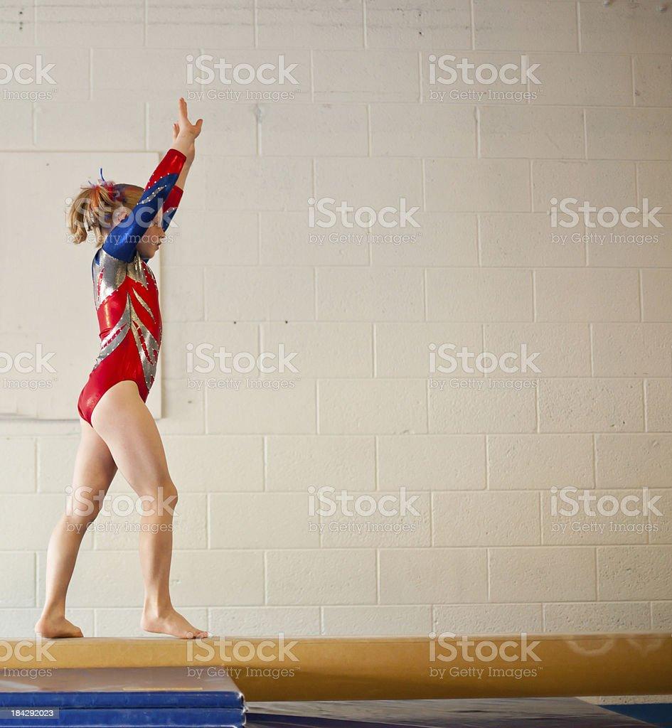 Young Gymnast Doing Balance Beam Routine stock photo