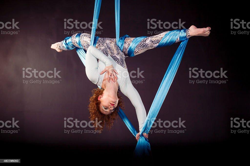 Gimnasta joven haciendo ejercicio de sedas aérea - foto de stock