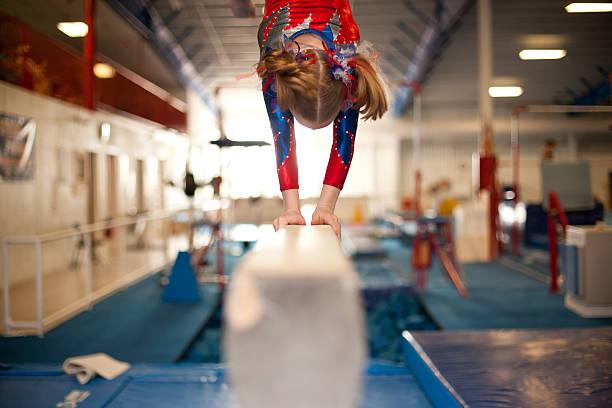 Young Gymnast Doing Handstand on Balance Beam stock photo