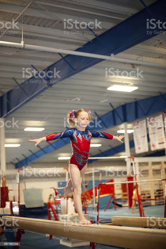 Young Gymnast Doing Routine on Balance Beam stock photo