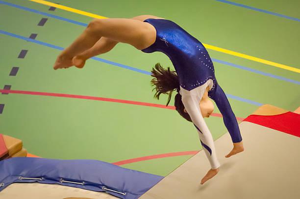 Young gymnast girl performing jump back handspring stock photo