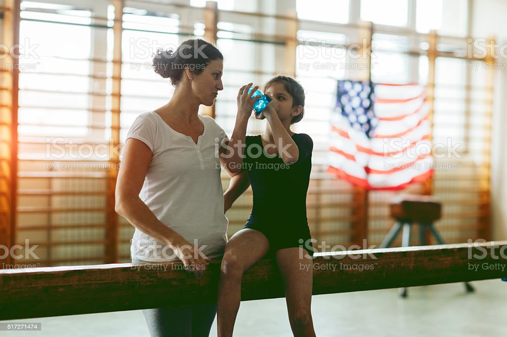 Young Gymnast Girl Talking With Her Coach stock photo