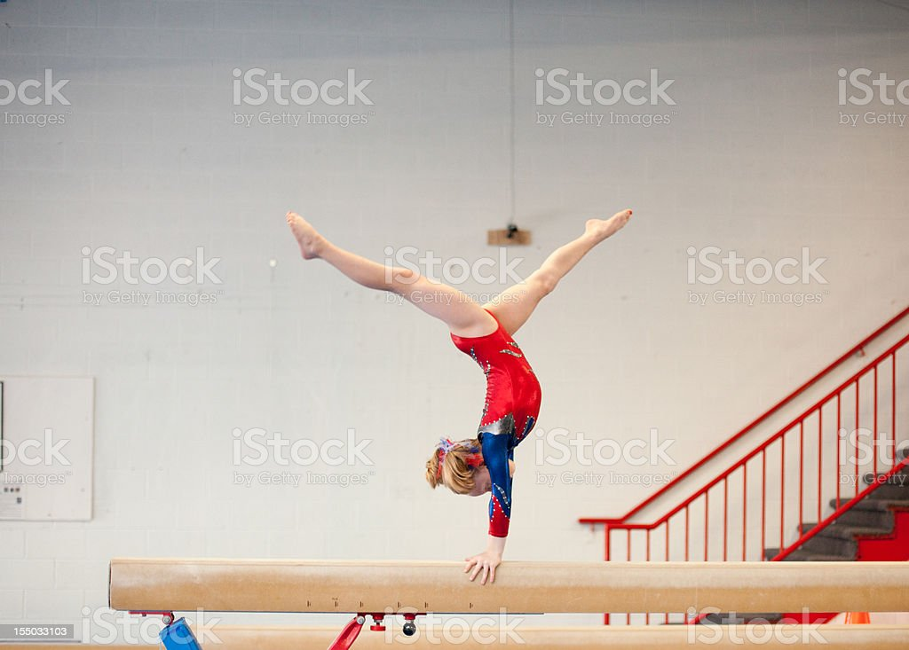 Young Gymnast in Handstand Split on Balance Beam stock photo