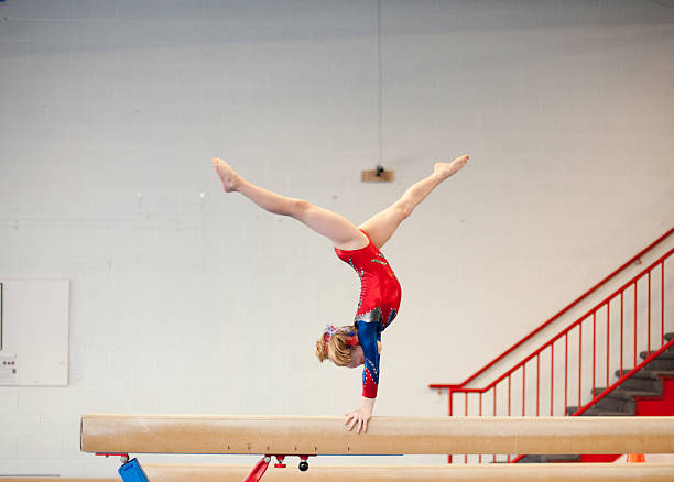 young gymnast in handstand split on balance beam - balance beam stock photos and pictures