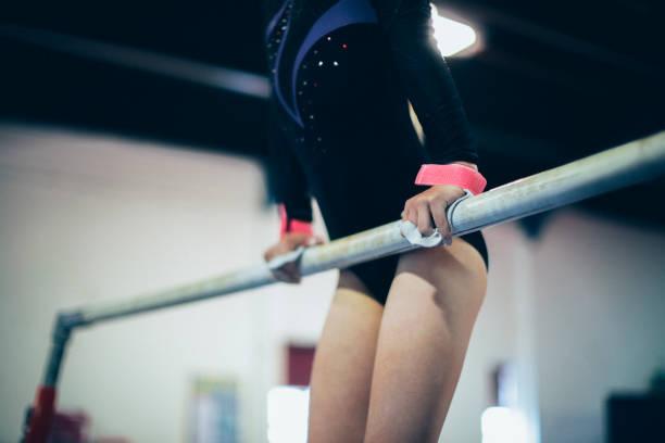 young gymnast on a horizontal bar - horizontal bar stock photos and pictures