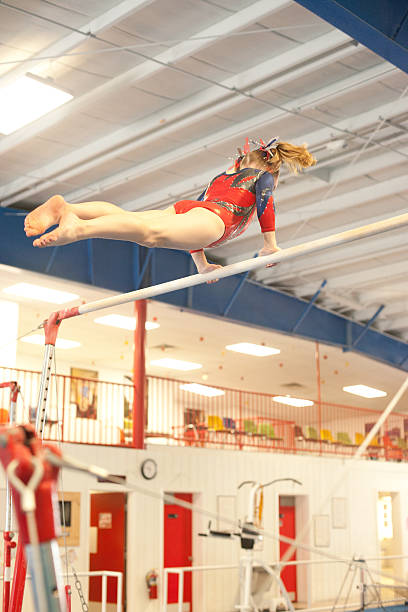 young gymnast on the uneven bars - uneven parallel bars stock photos and pictures