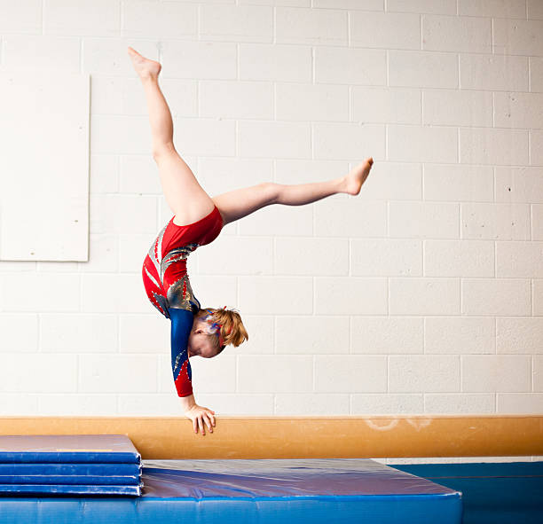 young gymnast performing walkover on balance beam - balance beam stock photos and pictures