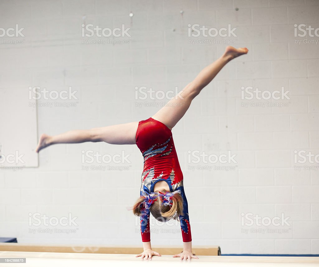 Young Gymnast Performs Cartwheel on Balance Beam stock photo
