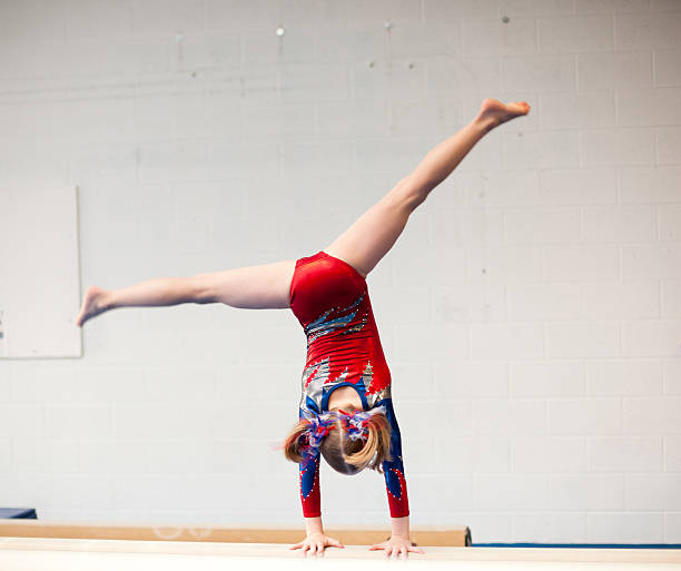 young gymnast performs cartwheel on balance beam - uneven parallel bars stock photos and pictures