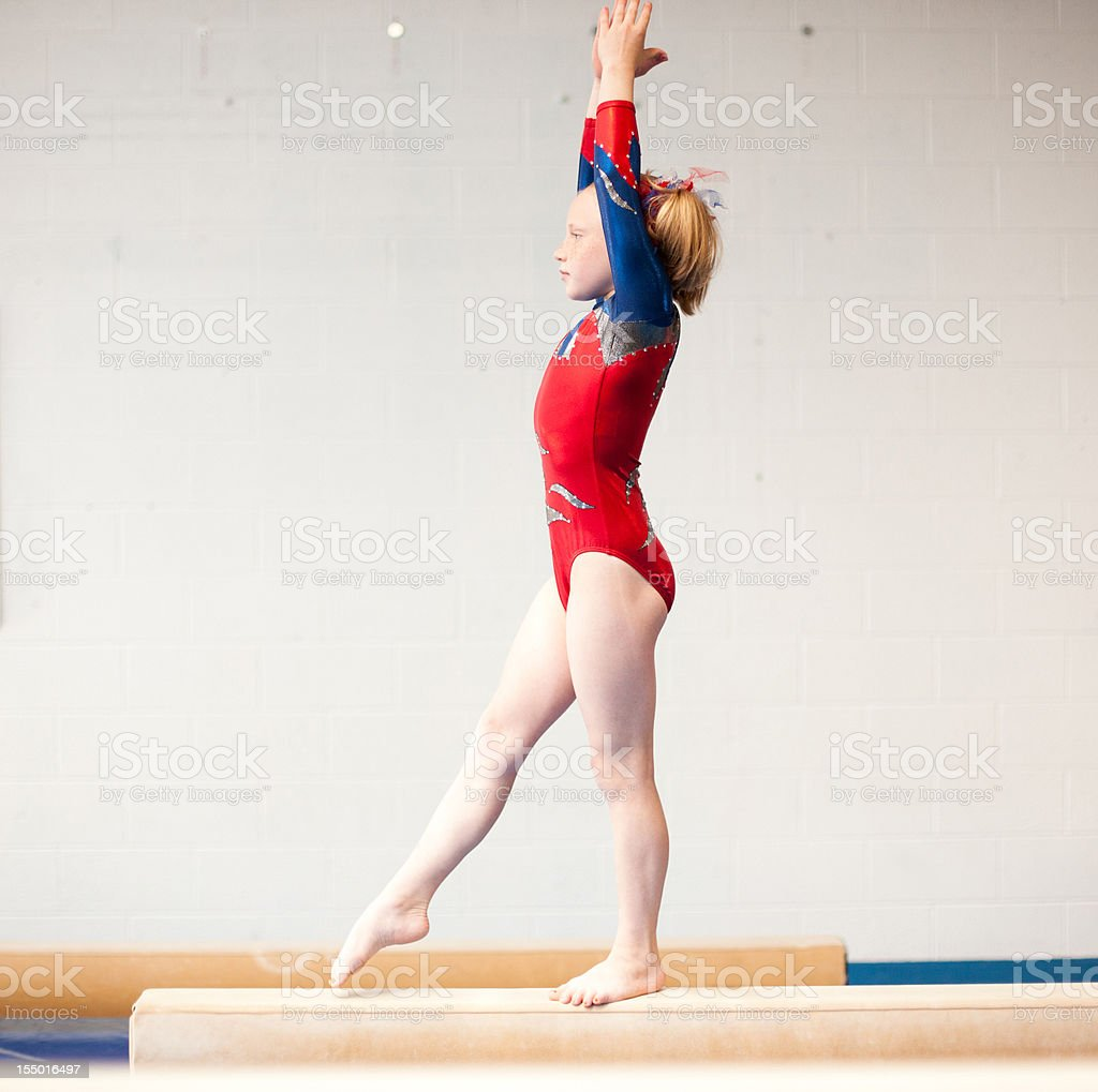 Young Gymnast Practicing Beam Routine stock photo
