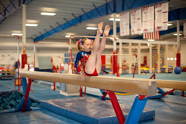 young gymnast practicing beam routine - uneven parallel bars stock photos and pictures