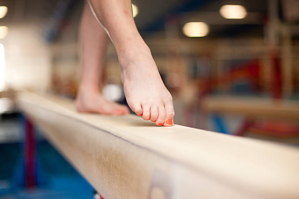 young gymnast toes on balance beam - balance beam stock photos and pictures