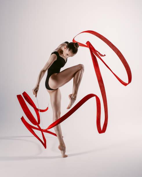 mujer joven gimnasta estiramiento y entrenamiento - gimnasia fotografías e imágenes de stock