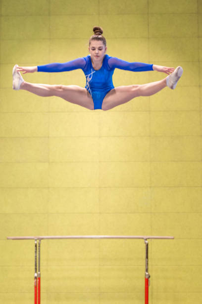 young gymnastics athlete doing the splits in mid-air - horizontal bar stock photos and pictures