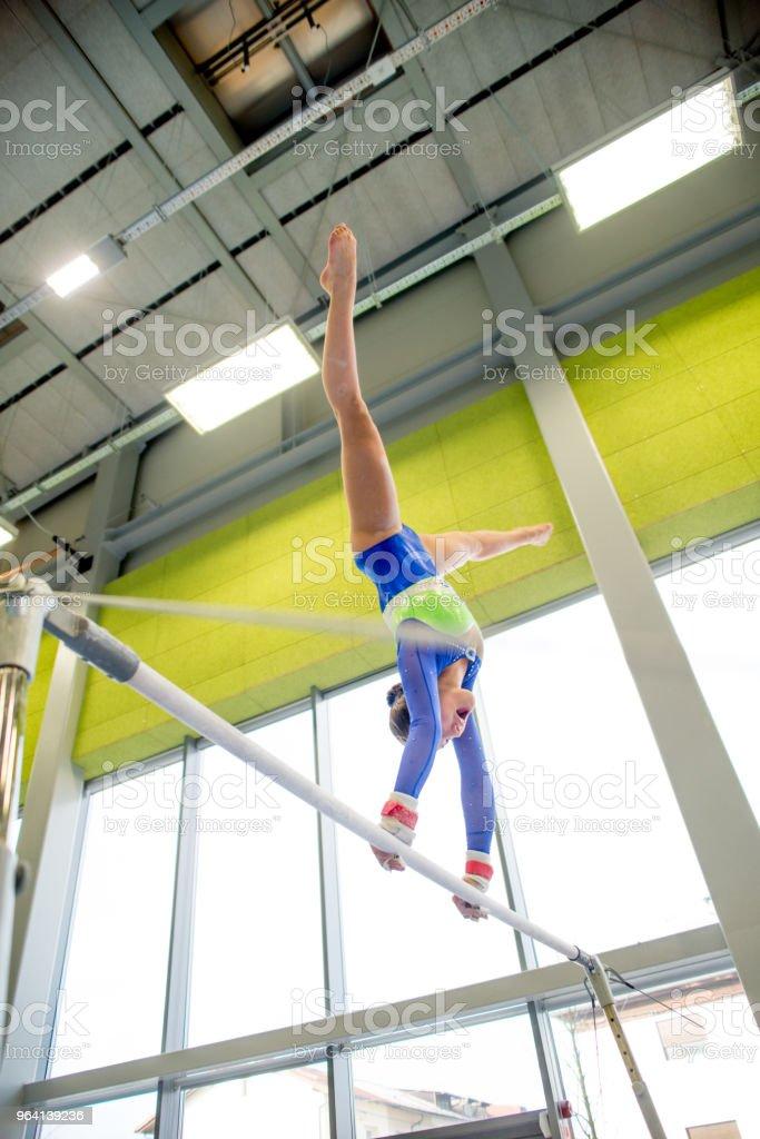Young Gymnastics Athlete Exercising On Horizontal Bar Stock Photo