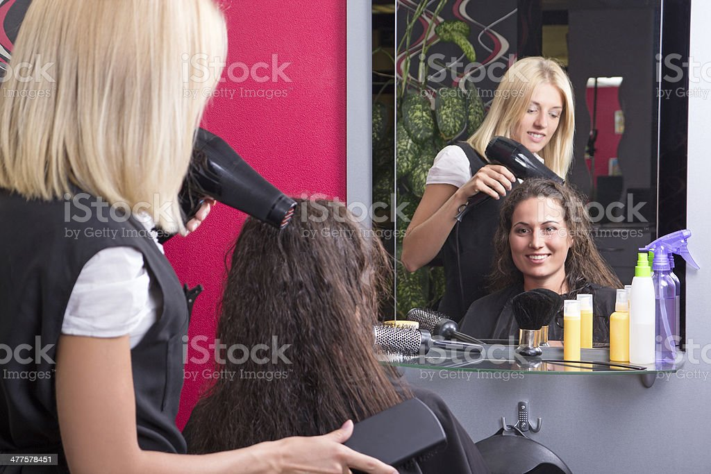 young hairdresser makes hairstyle for beautiful girl royalty-free stock photo
