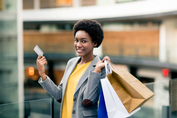 Young haitian woman carrying shopping bags and looking at camera stock photo