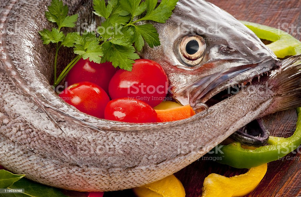 Young hake prepared for cooking with vegetables and herbs. stock photo