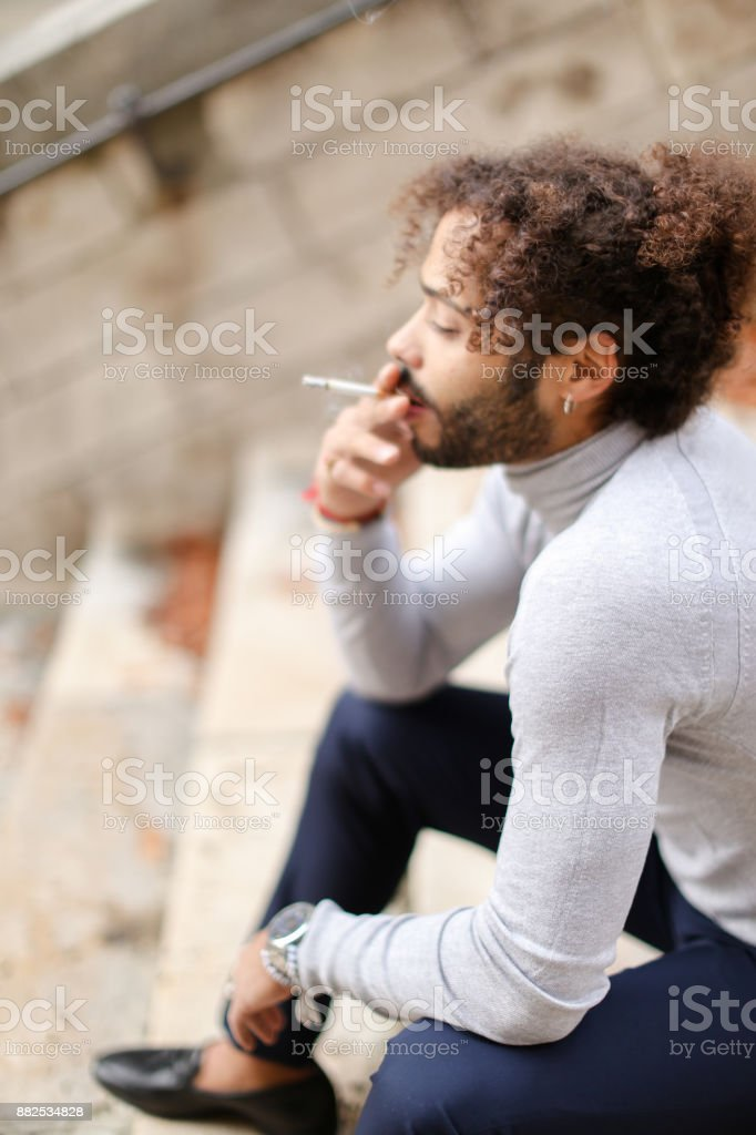 Young half Nigerian boy smiling on steps and looking aside stock photo