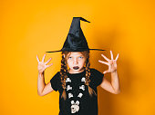 istock young halloween witch on orange background with black hat 1045448724