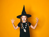 istock young halloween witch on orange background with black hat 1045448728