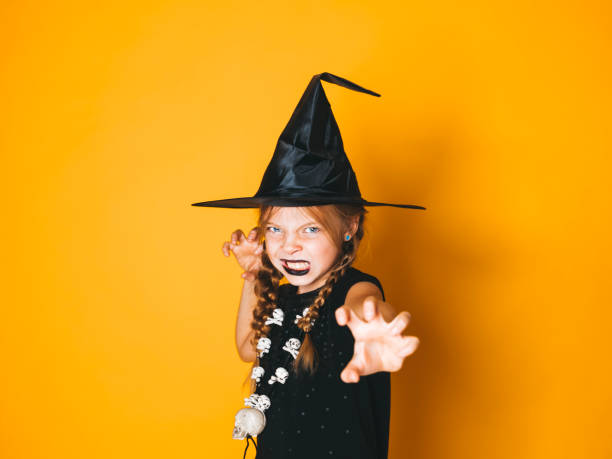young halloween witch on orange background with black hat stock photo