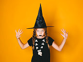istock young halloween witch on orange background with black hat 1045448748