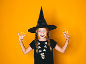 istock young halloween witch on orange background with black hat 1045448754